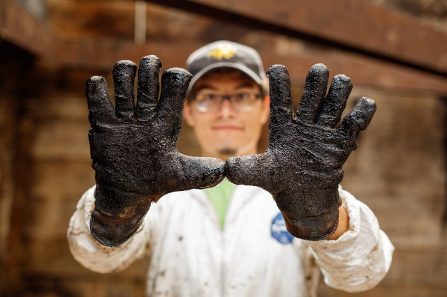 "Photography of man with gloved hands entirely covered in ""tar"""