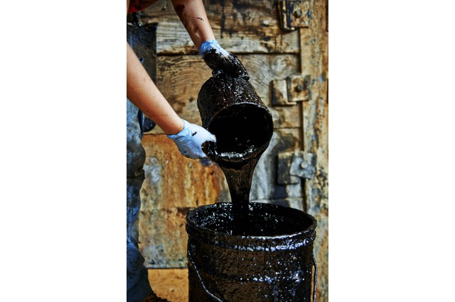 "Photograph of ""tar"" being poured from a bucket"