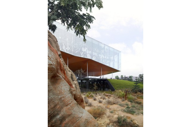 The existing building is opened up to the park with slits in the landscape that gives light in and views outwards. Above, a Pleistocene mural appears in solar pixels.