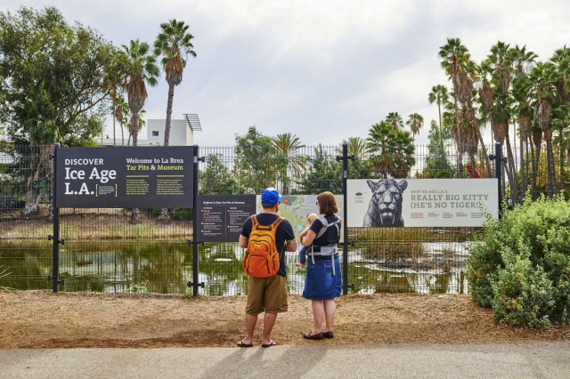 family standing in front of lake pit at la brea tar pits