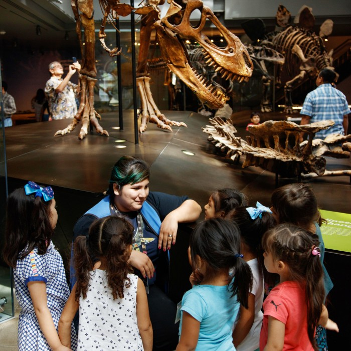 volunteer with kids in dinosaur hall NHM