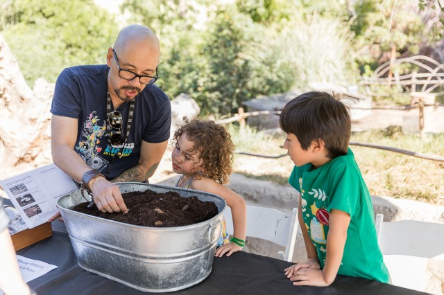 Volunteer with children in Nature Gardens