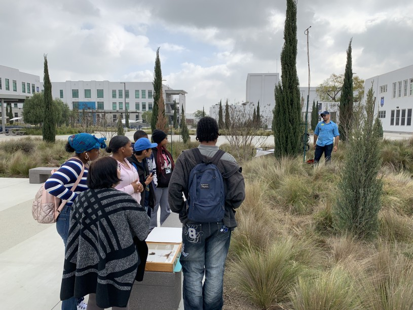 Miguel Ordeñana stands in a green space next to a bat detector while talking to a group of students